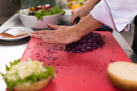 master chef hands cutting salad for a burger in the rastaurant kitchen