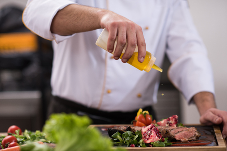 Chef finishing steak meat plate with Finally dish dressing and almost ready to serve at the table Stock Photo