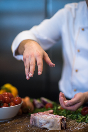 Master Chef hands putting salt on juicy slice of raw steak with vegetables around on a wooden table Stok Fotoğraf - 100783650