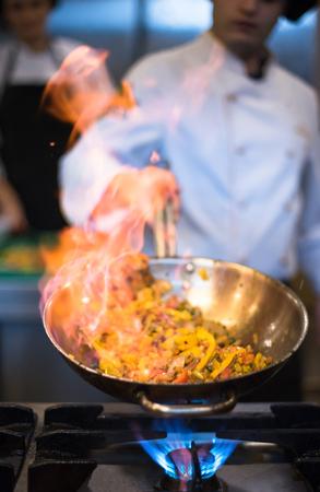 Chef-kok koken en doen flambe op eten in de keuken van het restaurant