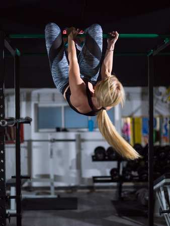 athlete woman doing abs exercises hanging upside down on horizontal bar at crossfitness gym