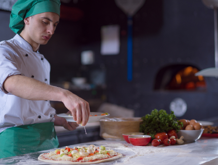 chef putting fresh vegetables over pizza dough on kitchen table Stockfoto - 101588097