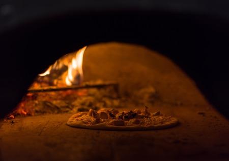 Chef poniendo deliciosa pizza en horno de leña de ladrillo con leña y llama Foto de archivo