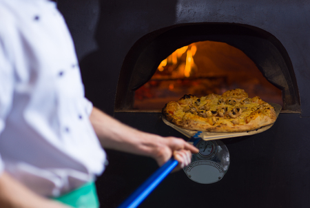 chef using special shovel to removing hot pizza from  stove where it was baked