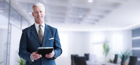 Portret starszego biznesmena za pomocą tabletu przed jego nowoczesnym biurze Zdjęcie Seryjne