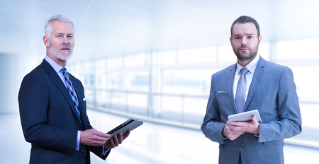 Portrait of two colleague businessmans using tablet in front of the modern IT company