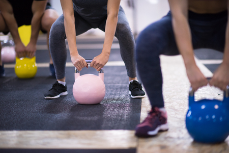 Group of healthy young athletes doing exercises with kettlebells at cross fitness studio