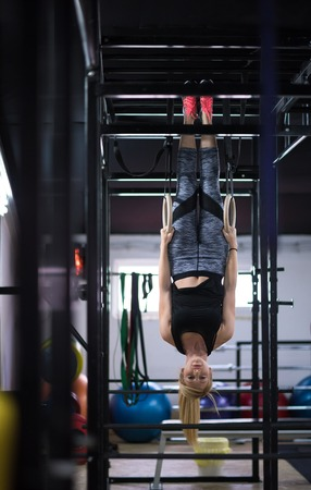 young athletic woman working out on gymnastic rings at the cross fitness gym