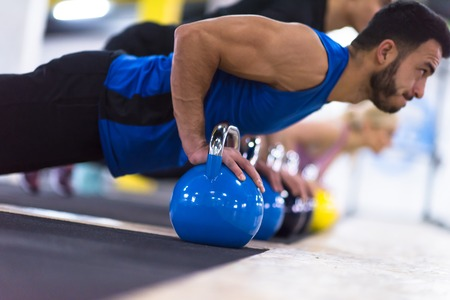 a group of young healthy athletes doing pushups with kettlebells at cross fitness gym Stock Photo