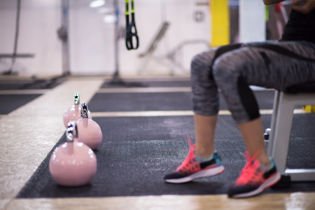 young  woman athlete exercise with fitness kettlebell at cross fitness gym