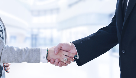 Businessman and businesswoman shaking hands after meetup with modern office in background