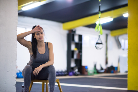 young athlete woman sitting and relaxing after exercise at cross fitness gym