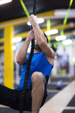 young muscular man doing rope climbing in cross fitness gym Stock Photo