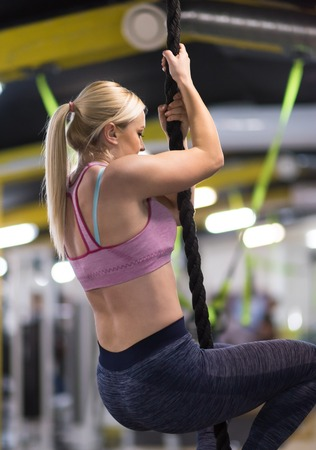 young muscular woman doing rope climbing in cross fitness gym Stock Photo