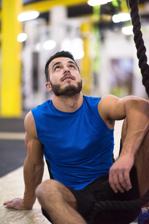 young muscular man sitting and relaxing before rope climbing in cross fitness gym