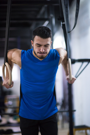 young athlete man working out pull ups with gymnastic rings at the cross fitness gym