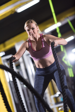 young fit athlete woman working out in functional training gym doing  battle ropes exercise as part of cross fitness training