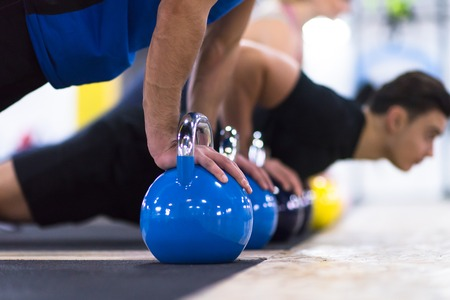a group of young healthy athletes doing pushups with kettlebells at cross fitness gym Foto de archivo