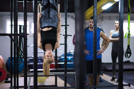 young athletic woman working out with personal trainer on gymnastic rings at the cross fitness gym