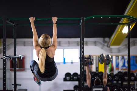 athlete woman doing abs exercises hanging upside down on horizontal bar at cross fitness gym Stock Photo