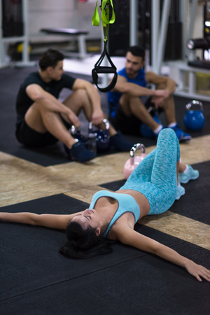 young athlete woman lying on the floor and relaxing before a hard training at cross fitness gym