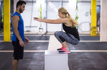 young athletic woman training with personal trainer  jumping on fit box at cross fitness gym