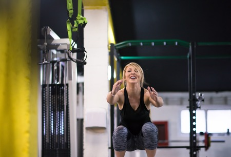 young athletic woman training  jumping on fit box at cross fitness gym