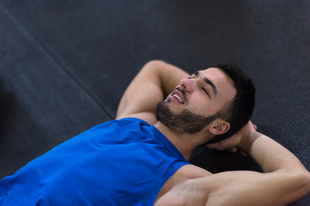 young athlete man lying on the floor and relaxing before a hard training at cross fitness gym