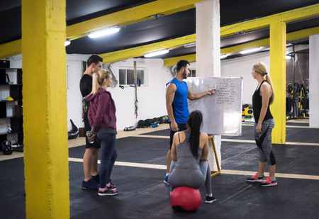 Training course.group of young athletes getting instructions from trainer before exercise at cross fitness gym Stock Photo