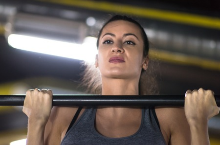 young muscular woman doing pull ups on the horizontal bar as part of Cross fitness Training