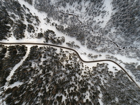 top view aerial drone flying above curvy road wind mountains and forest covered with snow on bad weather
