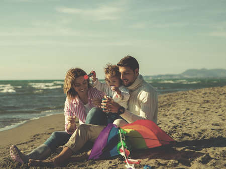 Family with little daughter resting and having fun making soap bubble at beach during autumn day colored filter Фото со стока