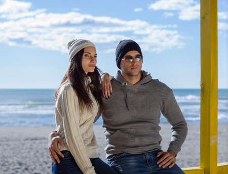 Happy couple enyojing time together on beach during autumn day Stockfoto