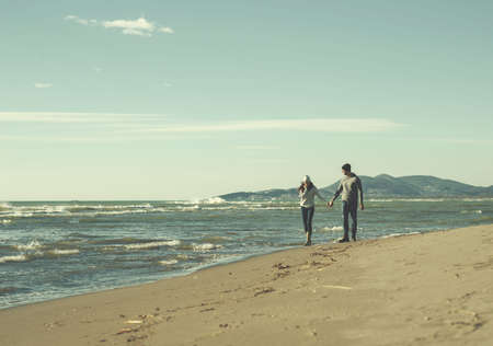 Young couple having fun walking and hugging on beach during autumn sunny day colored filter 스톡 콘텐츠