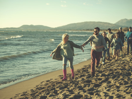 group of young friends spending day together running on the beach during autumn day colored filter