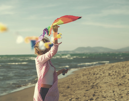 Beautiful Young Woman Holding A Kite at Beach on autumn day colored filter Stock Photo
