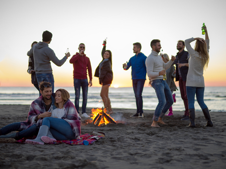 Young Couple Sitting with friends Around Campfire on The Beach At sunset drinking beer Stok Fotoğraf - 105989001