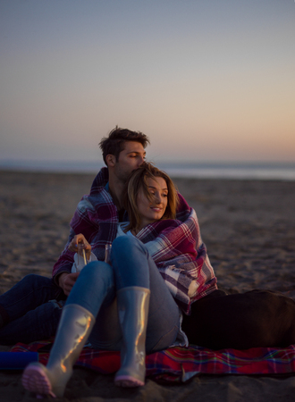 Young Couple Relaxing By The Fire, Drinking A Beer Or A Drink From The Bottle. Stock Photo