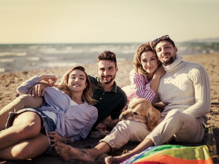 Group Of Young Friends Spending The Day On A Beach during autumn day colored filter Stock Photo