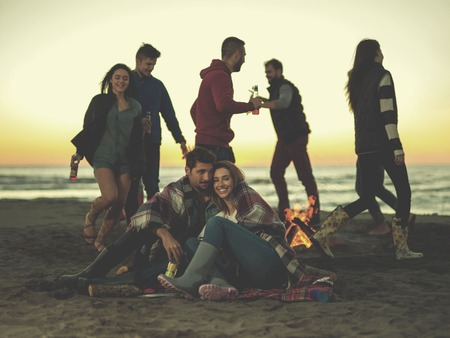 Young Couple Sitting with friends Around Campfire on The Beach At sunset drinking beer colored filter Stock Photo