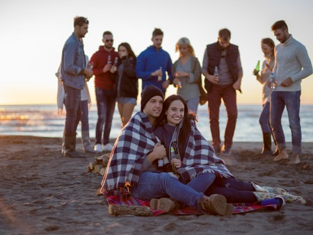 Young Couple Sitting with friends Around Campfire on The Beach At sunset drinking beer Stock Photo