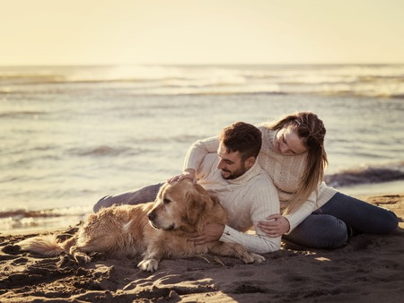 Couple With A Dog enjoying time  together On The Beach at autumn day colored filter