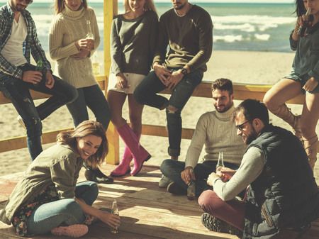 Happy Group Of Friends Hanging Out At Beach House having fun and drinking beer on autumn day colored filter Stock Photo