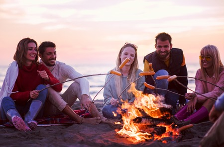 Group of young friends sitting by the fire at autumn beach, grilling sausages and drinking beer, talking and having fun filter Stock Photo - 106056403