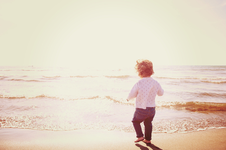 Adorable little girl having fun at beach during autumn day. Happy baby by the sea or ocean filter