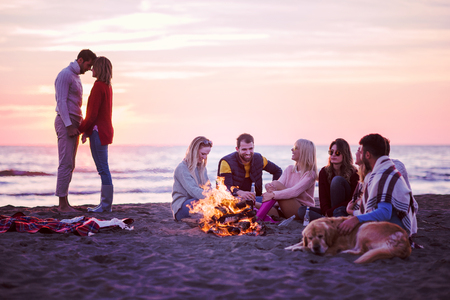 Young Couple enjoying with friends Around Campfire on The Beach At sunset drinking beer filter