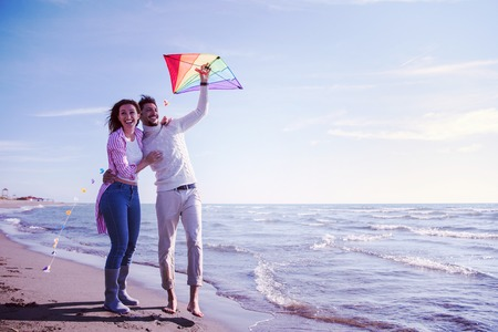 Young Couple having fun and Playing With A Kite On The Beach at autumn day filter Stock Photo - 106057726