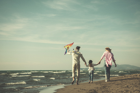 young family with kids resting and having fun with a kite at beach during autumn day filter Stock Photo