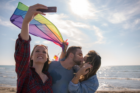group of young friends making selfie while playing with kite on a beach during sunny autumn day