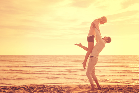 Young couple having fun walking and hugging on beach during autumn sunny day filter